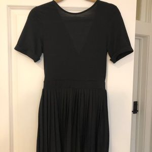 Black mini dress with pleated skirt.